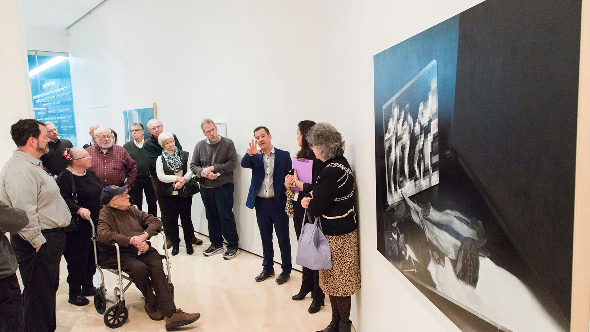 Group of adults listening to a lecture in a gallery