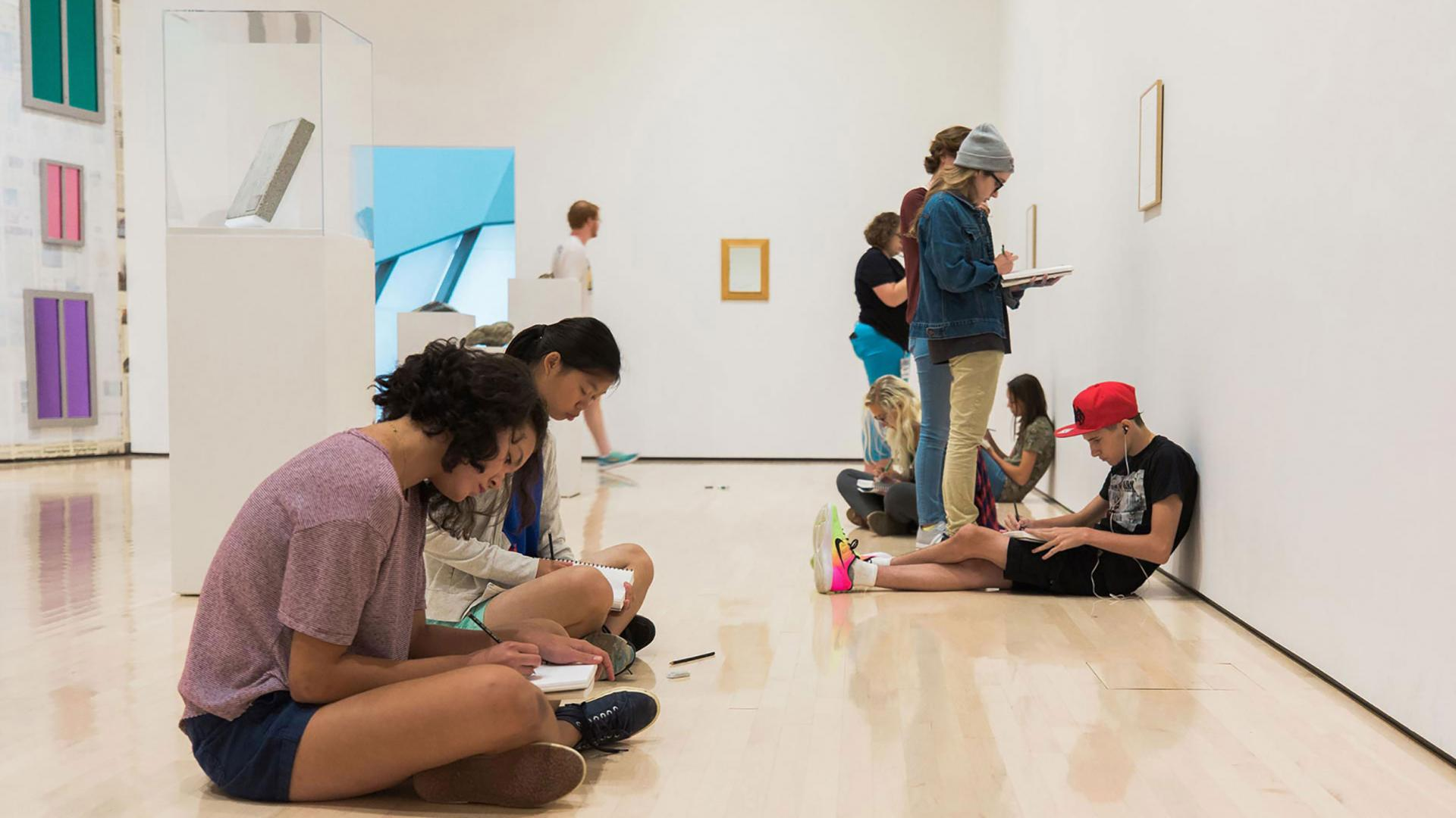 People sitting on a art gallery floor