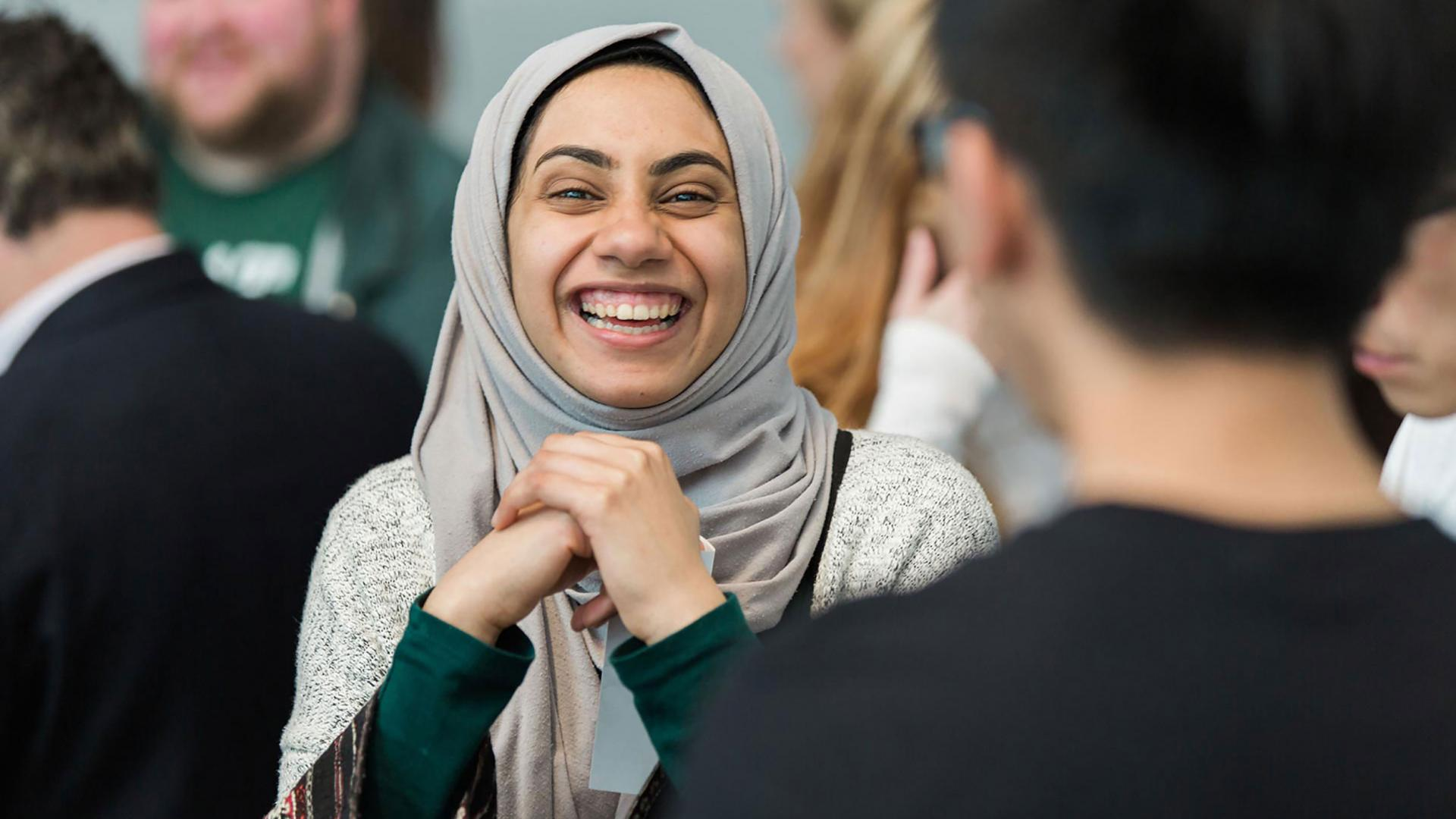 A woman in a head scarf smiling brightly