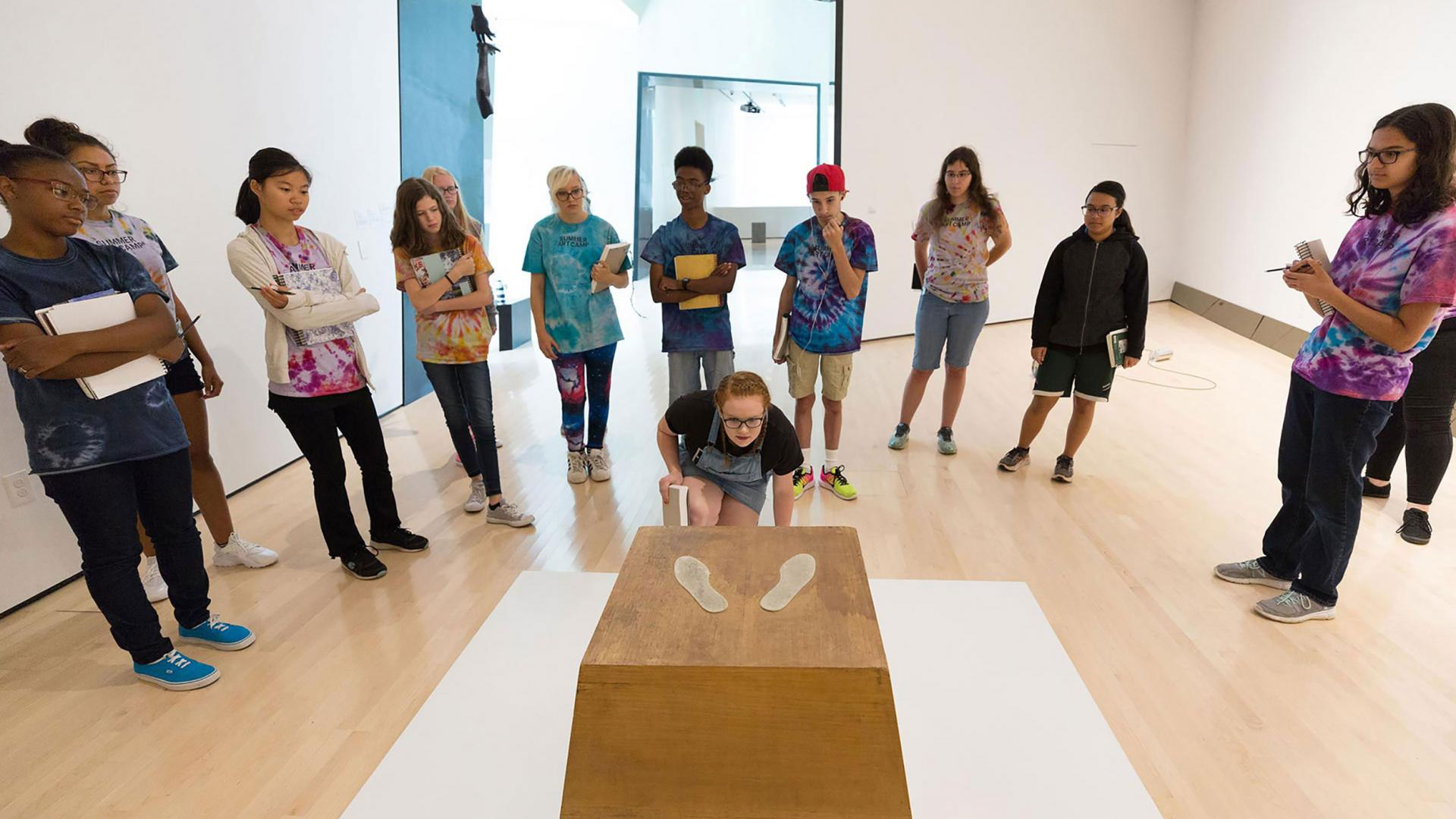 Students standing in a semi circle viewing artwork